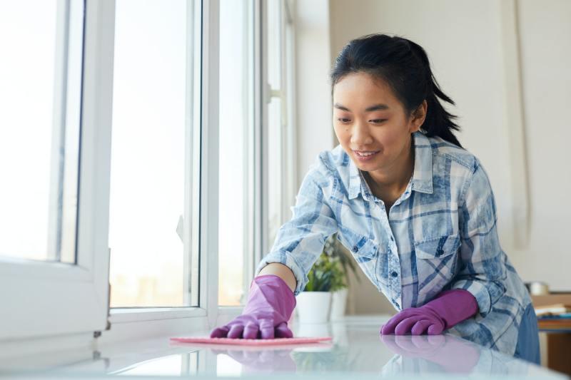 Young Asian Woman Washing Windows at Home