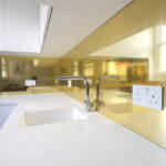 A Picture of A Kitchen with Golden Splashback