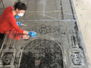 A female artist using brushes to create a design on a silvered glass surface