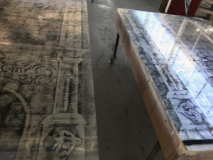 Two gilded glass panels with fireplace designs etched on them laying on a table.