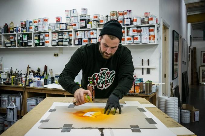 Snik hand finishing prints in the studio