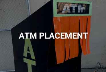"""A customized outdoor ATM kiosk. the body is a reflective black and """"ATM"""" is painted in neon green vertically along the side and horizontally along the front. There are neon orange tassels hanging for user privacy and weather protection."""