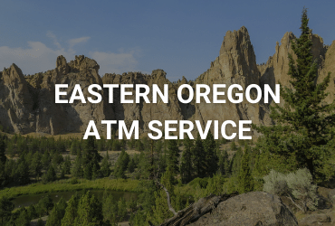 """The words """"Eastern Oregon ATM Service"""" are across the image in white. A sunny day in the rock canyons of Eastern Oregon. Large rock formations line the image, in the foreground are spiny pine trees."""