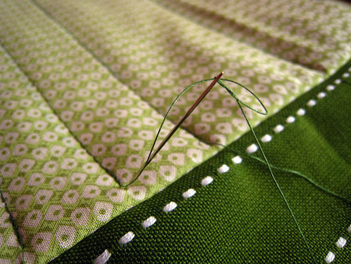 Needle case pocket; hand sewing the tail of the machined thread