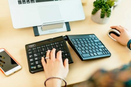 employee at desk typing on ergonomic keyboard