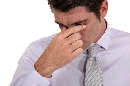 employee rubbing eyes after feeling eye strain