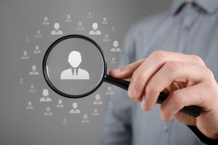 image symbolizing analyze your results: man holding magnifying glass over icons of people