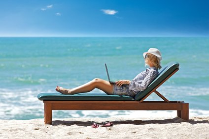 woman using laptop on vacation at beach