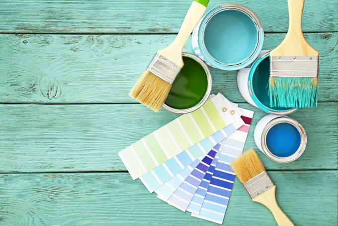 Cans of paint with brushes and palette samples on wooden background