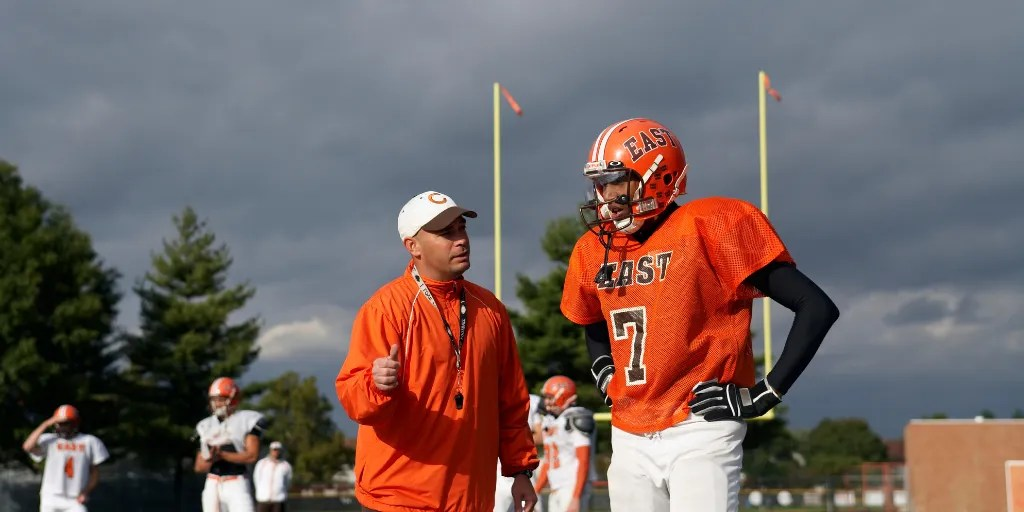 Head Football Coach is using his practice plan to give instruction to a player
