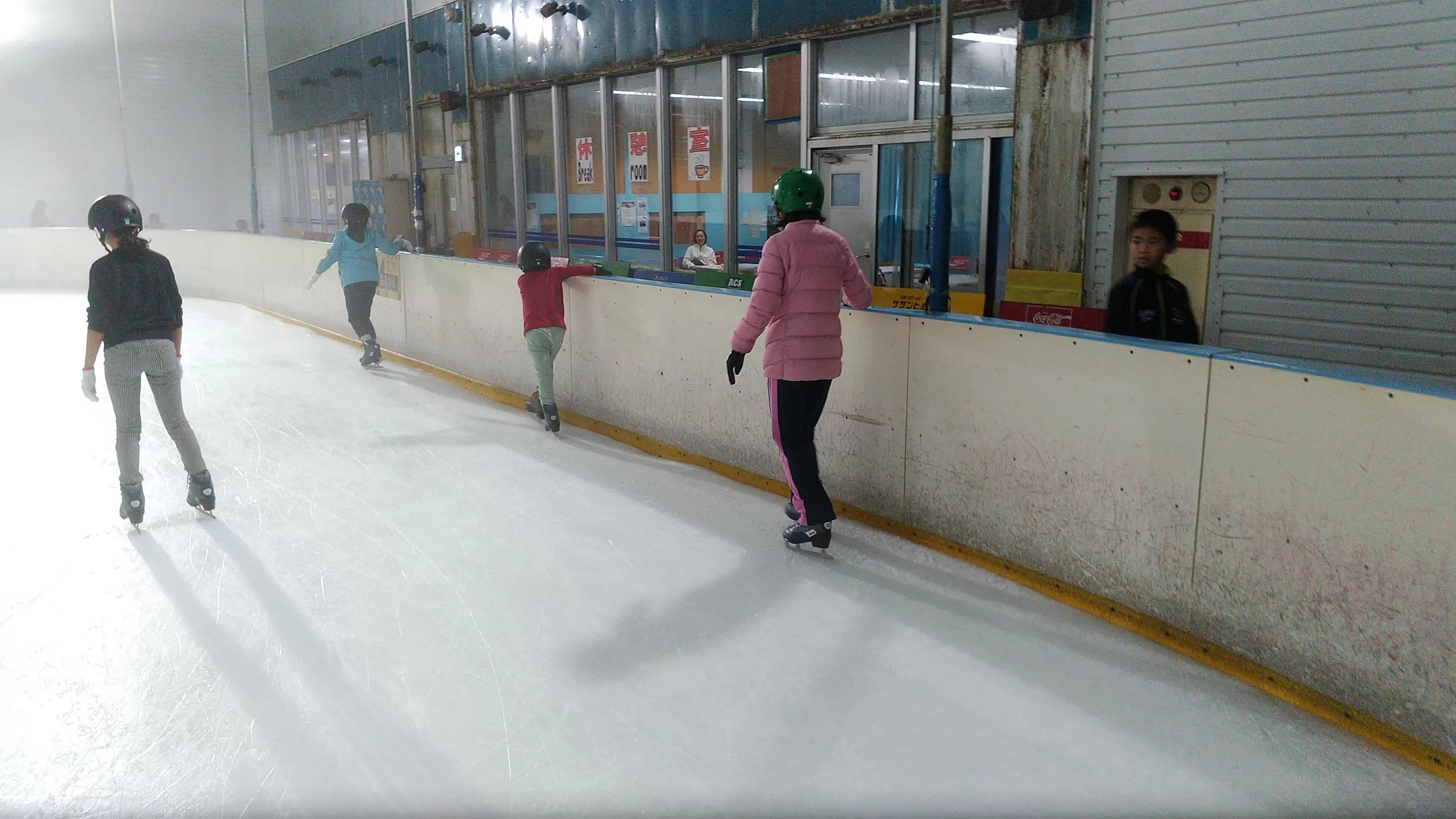 My children wear ice skates and have a first experience with ice skating