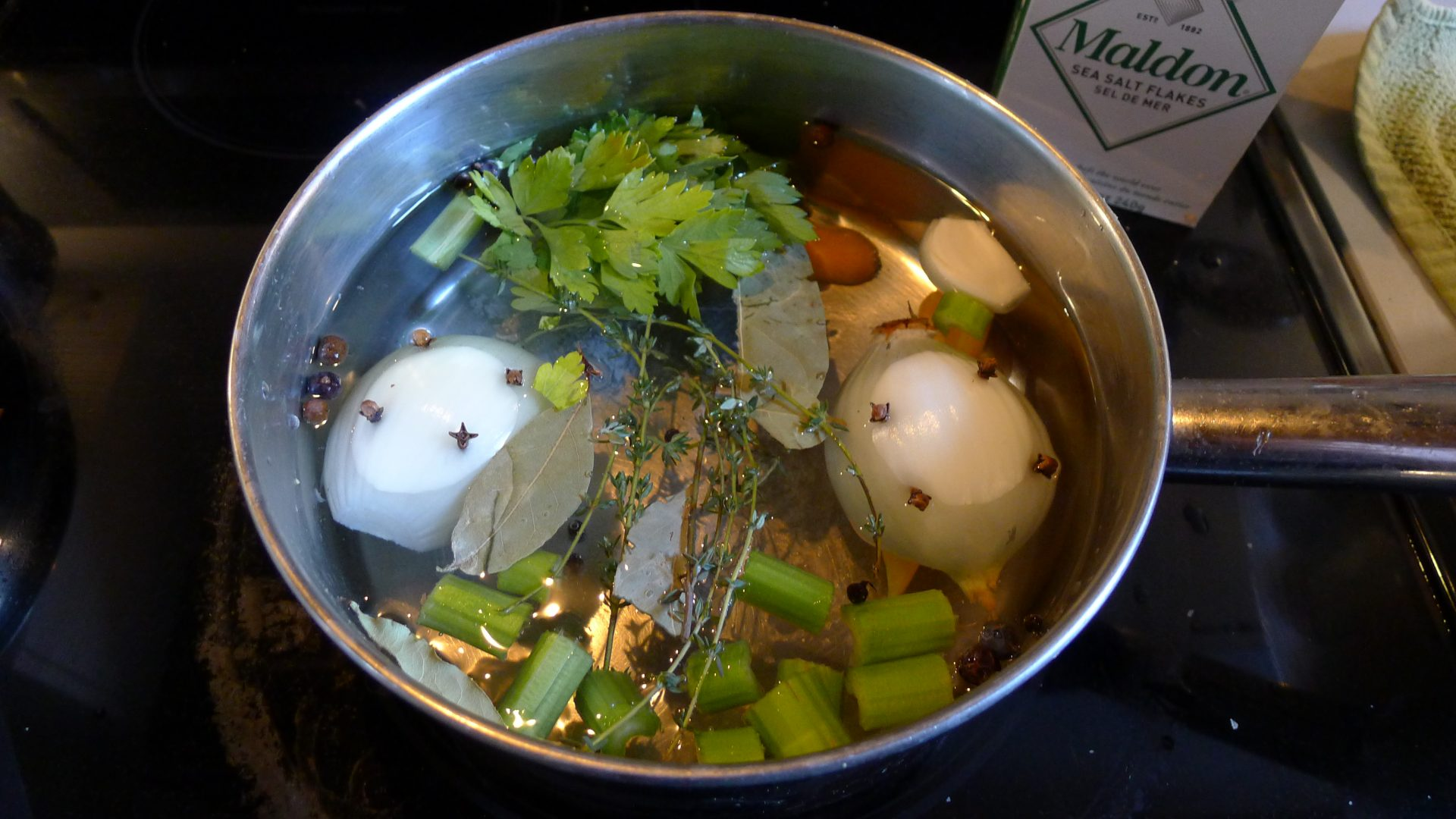 Although many recipes recommend the brining of tongue no matter the beast of its provenance, I chose to forego such complications, making up for this with the addition of a healthy amount of salt to my poaching liquid. Here you can see the onion (halved and spiked with eight cloves), two ribs of celery, a few sprigs of fresh thyme, eight juniper berries, eight black peppercorns, eight allspice, four bay leaves, a handful of parsley leaves and stalks, a couple of ribs of celery (chopped), and one peeled carrot (halved) that make up the aromatics.