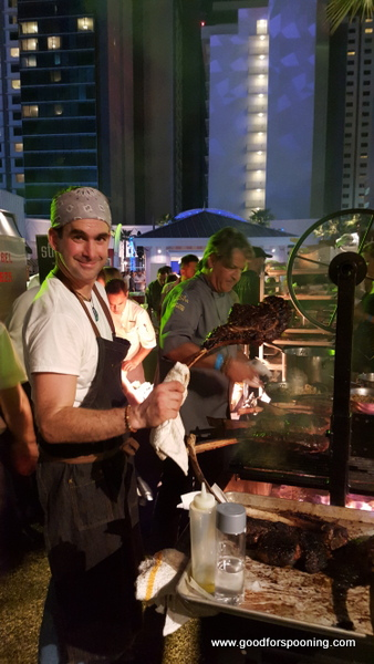 Chef Kim Canteenwalla in the back ground while one of the grillmasters shows off a Tomahawk Ribeye.