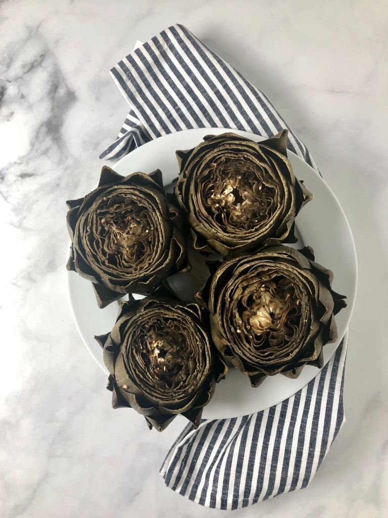 Four roasted artichokes on plate