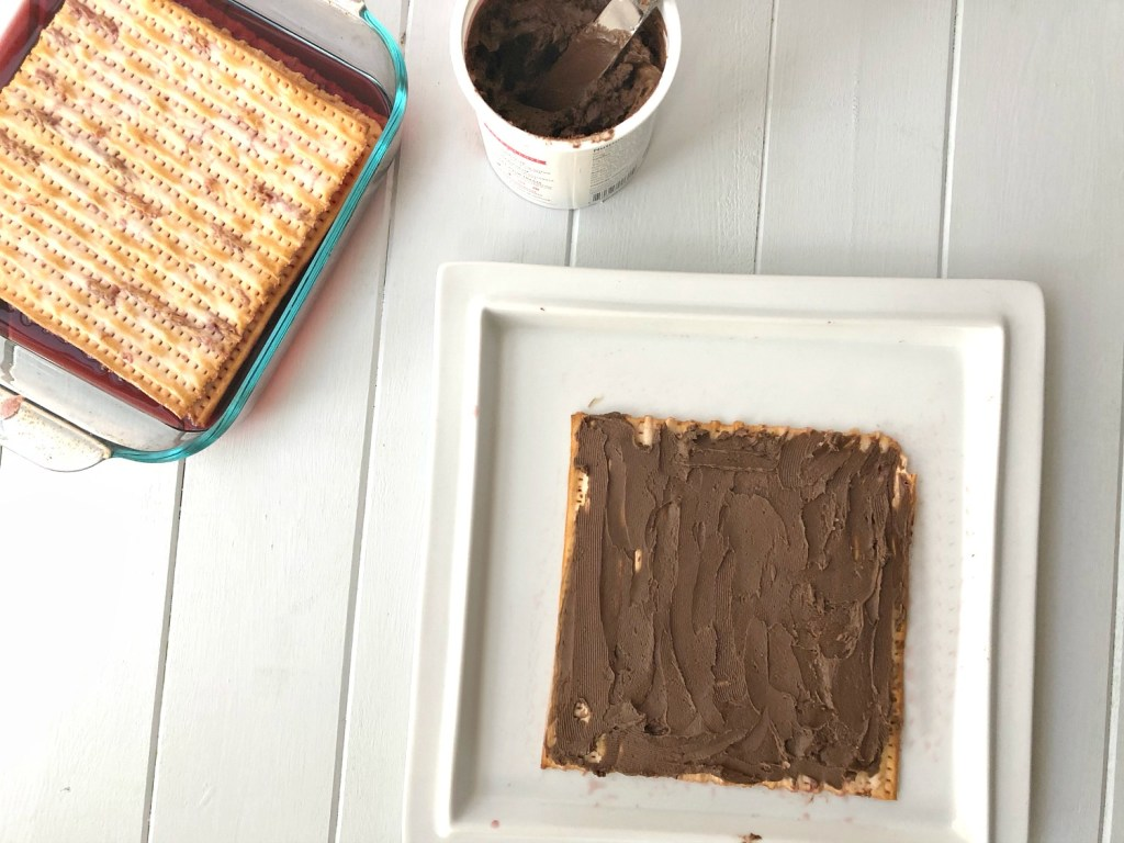 Matzah soaking in wine while cake is being layered with frosting