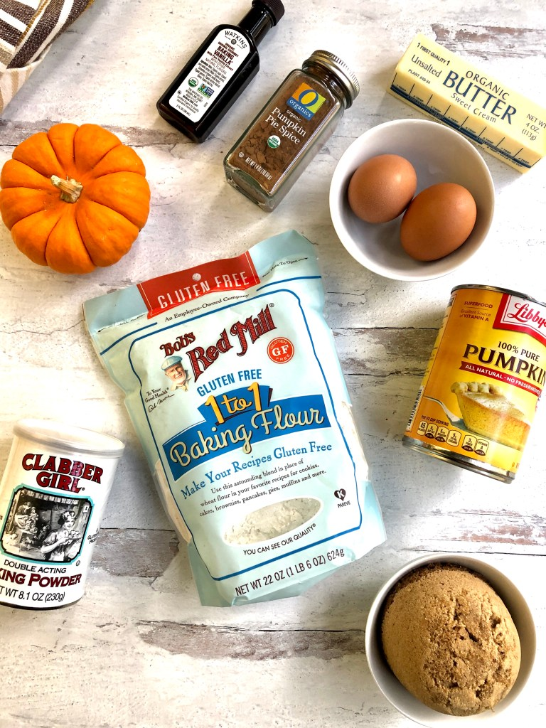 Picture of ingredients needed for pumpkin muffins including flour, eggs, pumpkin puree, vanilla and more