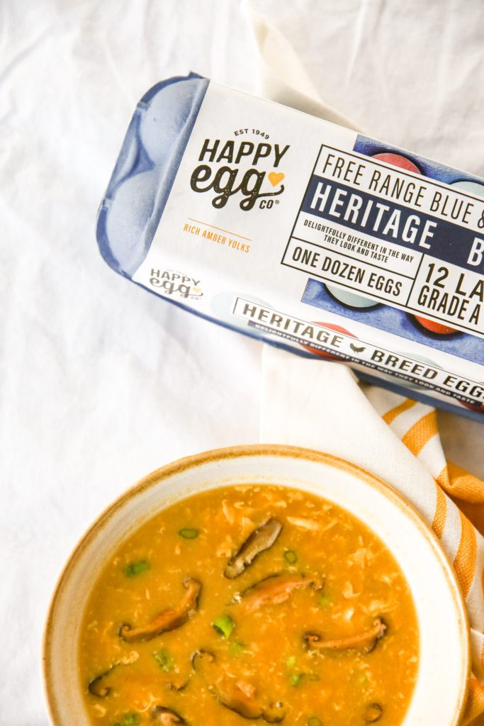Happy Eggs Heritage Egg Carton with egg drop soup in foreground