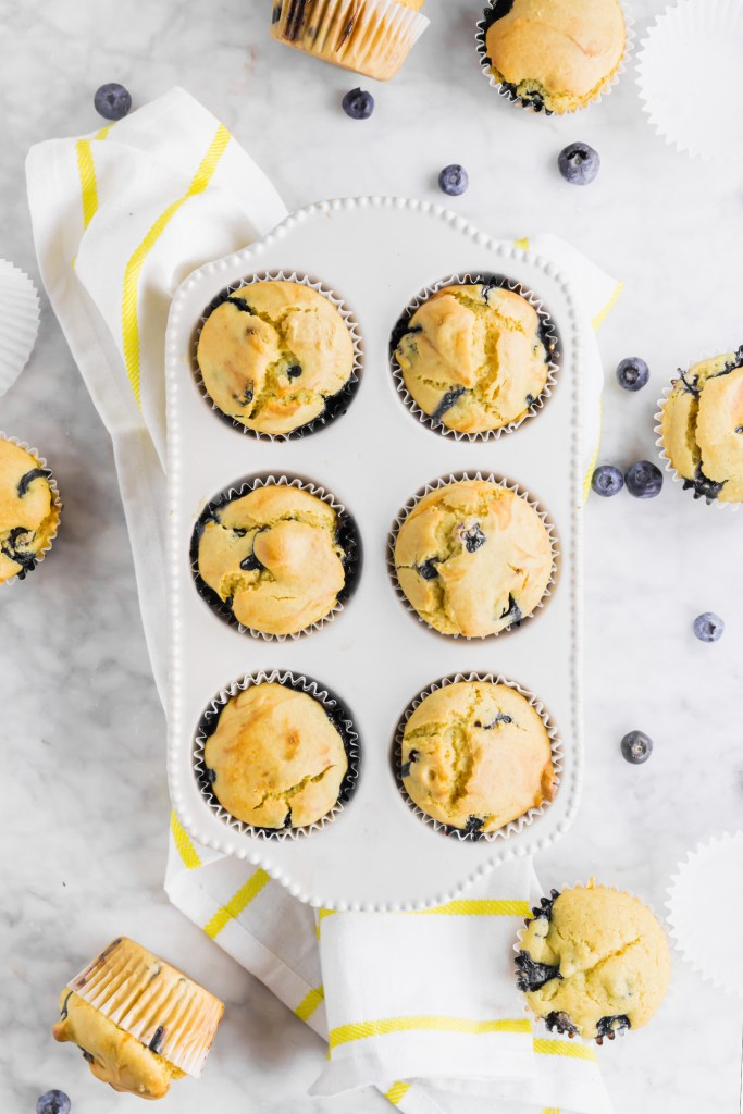 Overhead shot of baked gluten-free blueberry muffins inside the muffin tin surrounded by fresh blueberries.