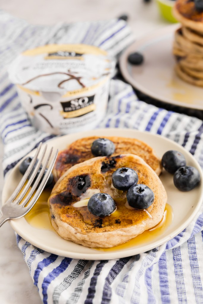 Picture of gluten-free pancakes with So Delicious coconutmilk yogurt in background and topped with blueberries