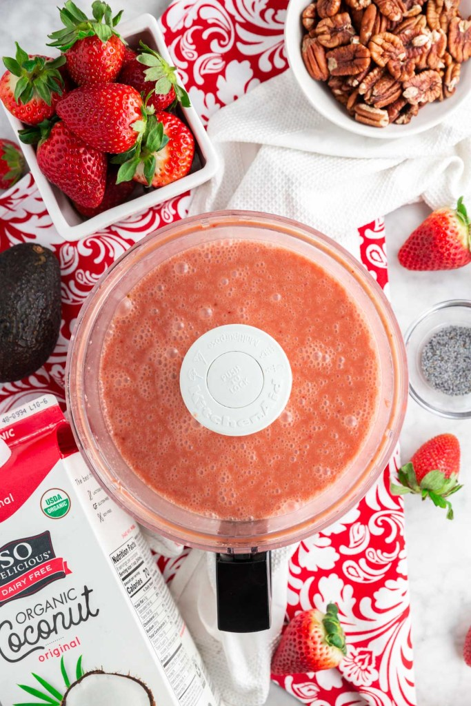 The strawberry coconut poppy seed salad dressing inside a food processor already processed.