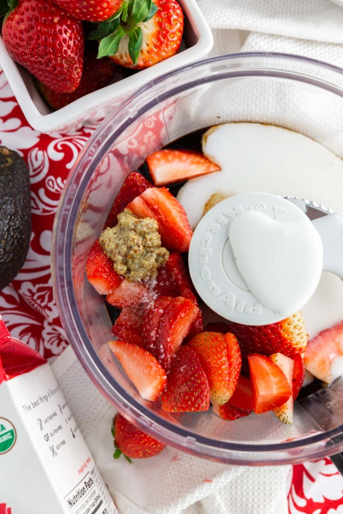 All the ingredients needed to make the strawberry coconut poppy seed salad dressing inside a food processor before being processed.