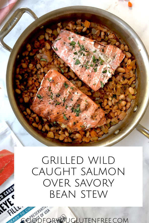 Pin image featuring two cooked wild salmon fillets served over the bean stew inside a large saute pan.