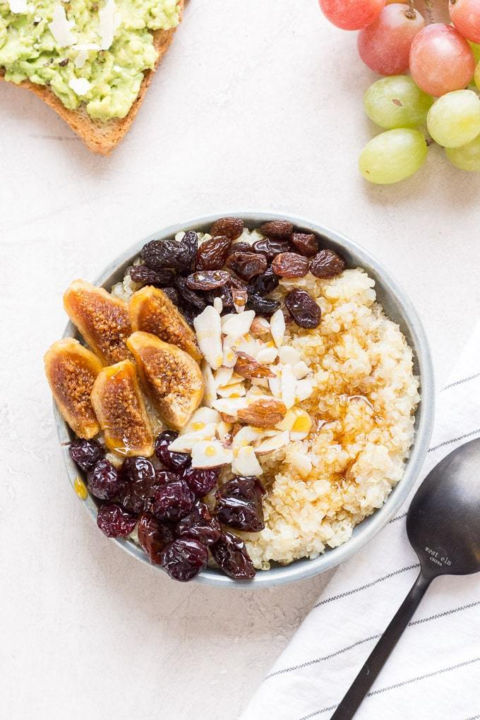 Picture of a bowl of warm quinoa with figs, raisins, dried cranberries and slivered almonds - as well a drizzle of maple syrup - on top.