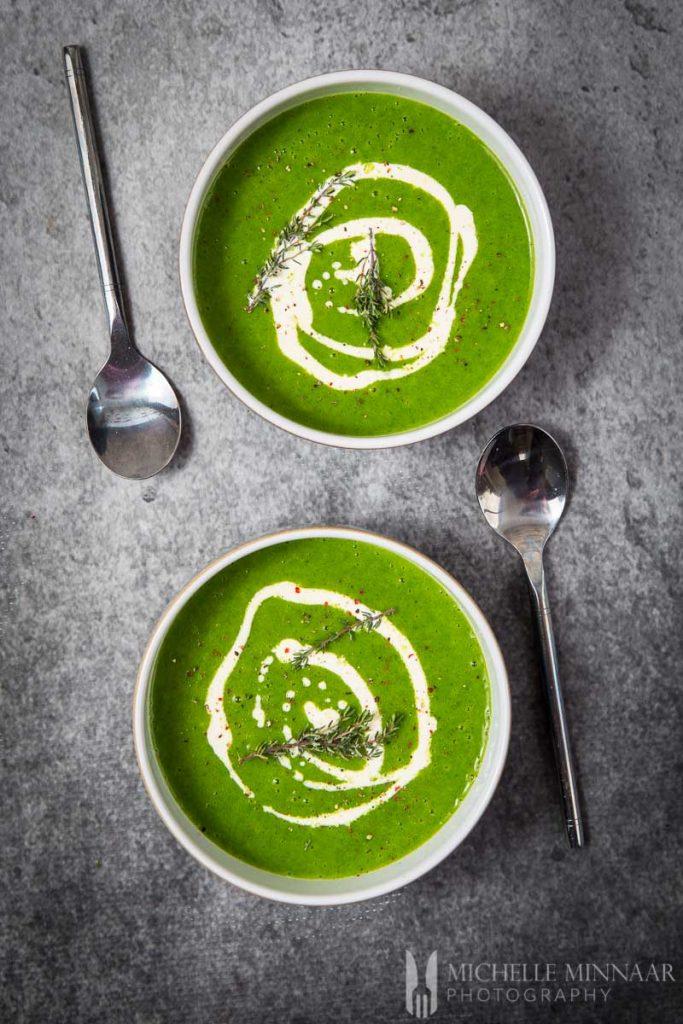 Beautiful green watercress soup with swirls of white cream inside.