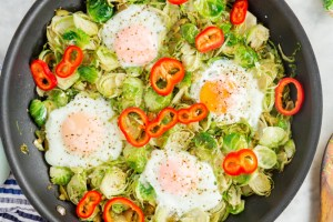 upclose picture of cooked eggs inside skillet with brussel sprouts and topped with red peppers