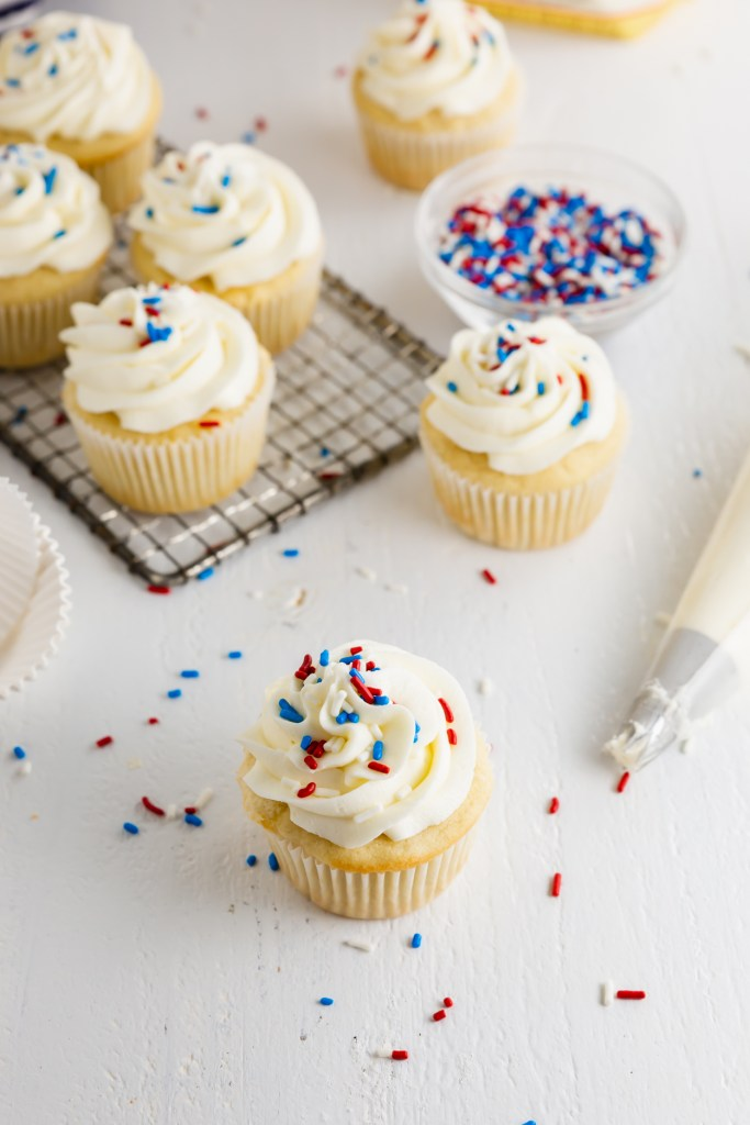 Cupcake with frosting and red, white and blue sprinkles.