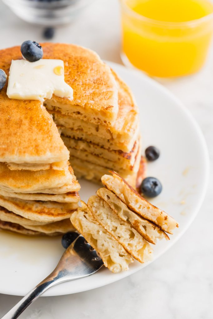 Stack of fluffy gluten-free pancakes with a slice taken out of it