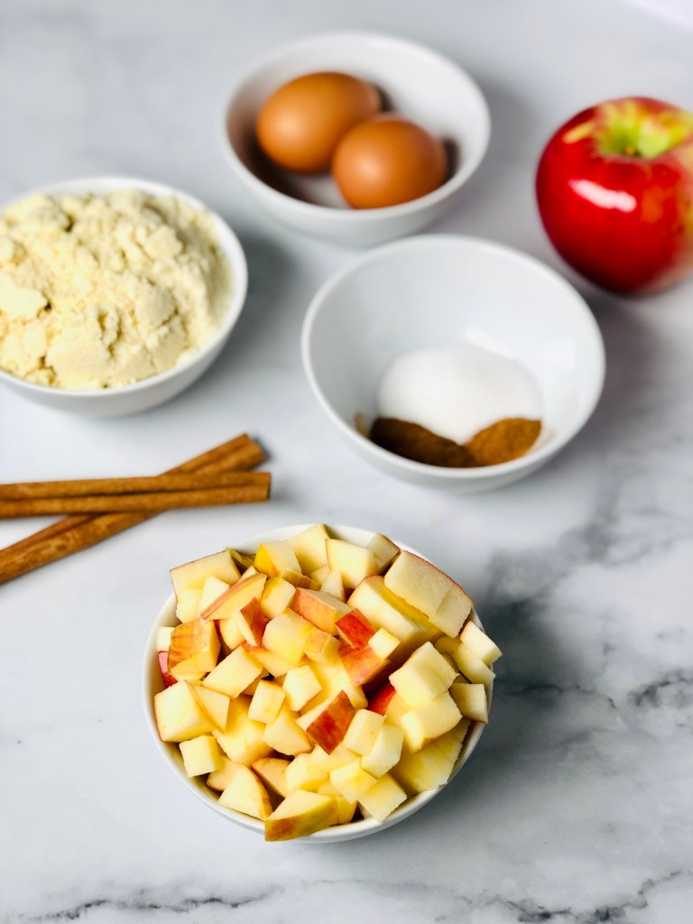 Picture of diced apples, cinnamon, sugar, almond flour and eggs - all the ingredients needed for the almond flour muffins