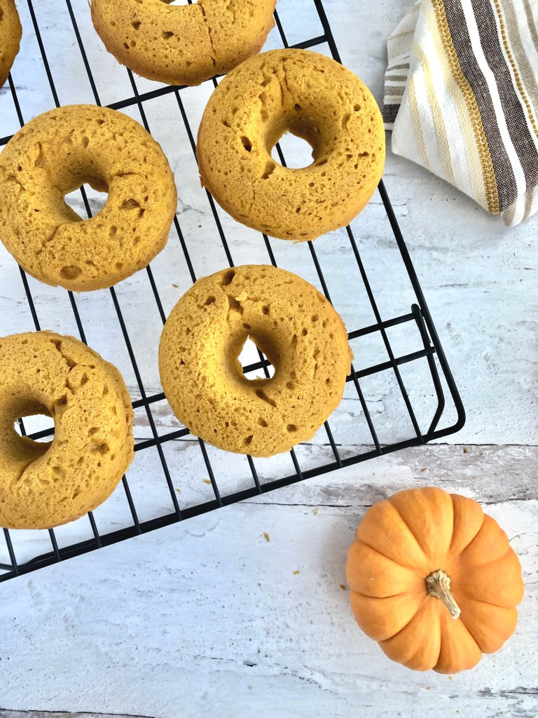 Spongy looking pumpkin donuts cooling on a wire rack