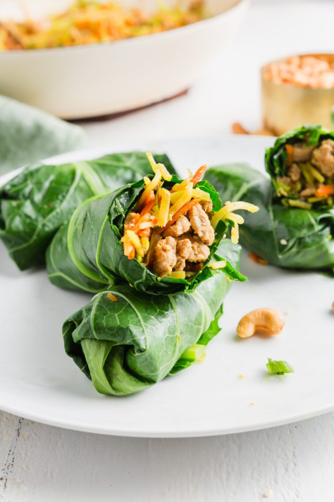 Wrapped collard green with egg roll filling showing in the middle