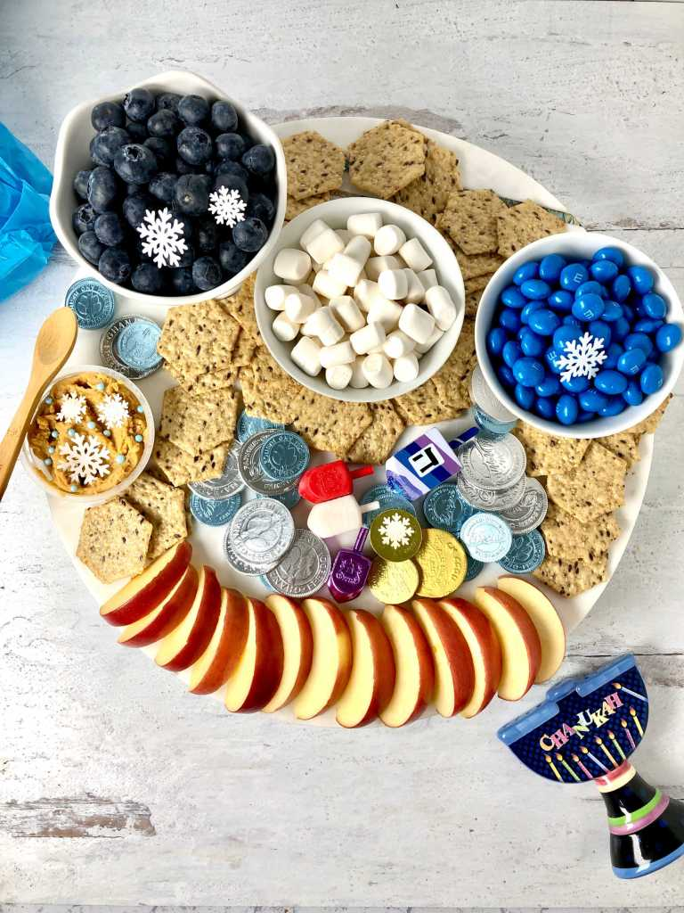 Picture of Hanukkah themed snack board with crackers, marshmallows, blue M&M, apples slices, blueberries and more.