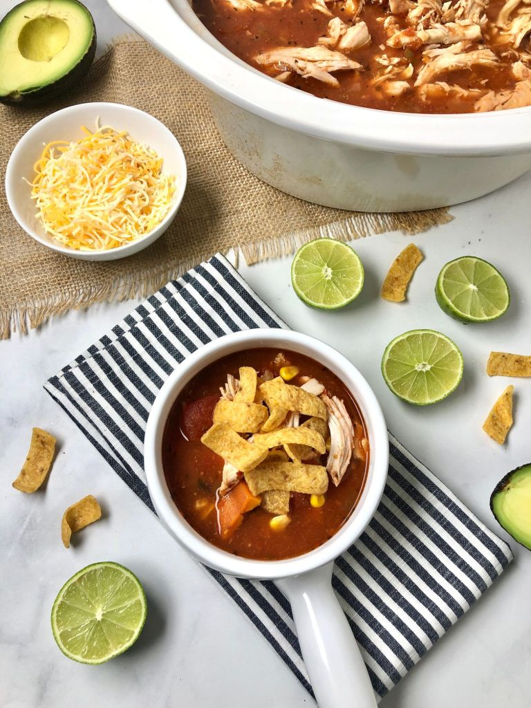 Overhead picture of the chicken enchilada soup topped with tortilla strips and served with avocado and lime and cheese