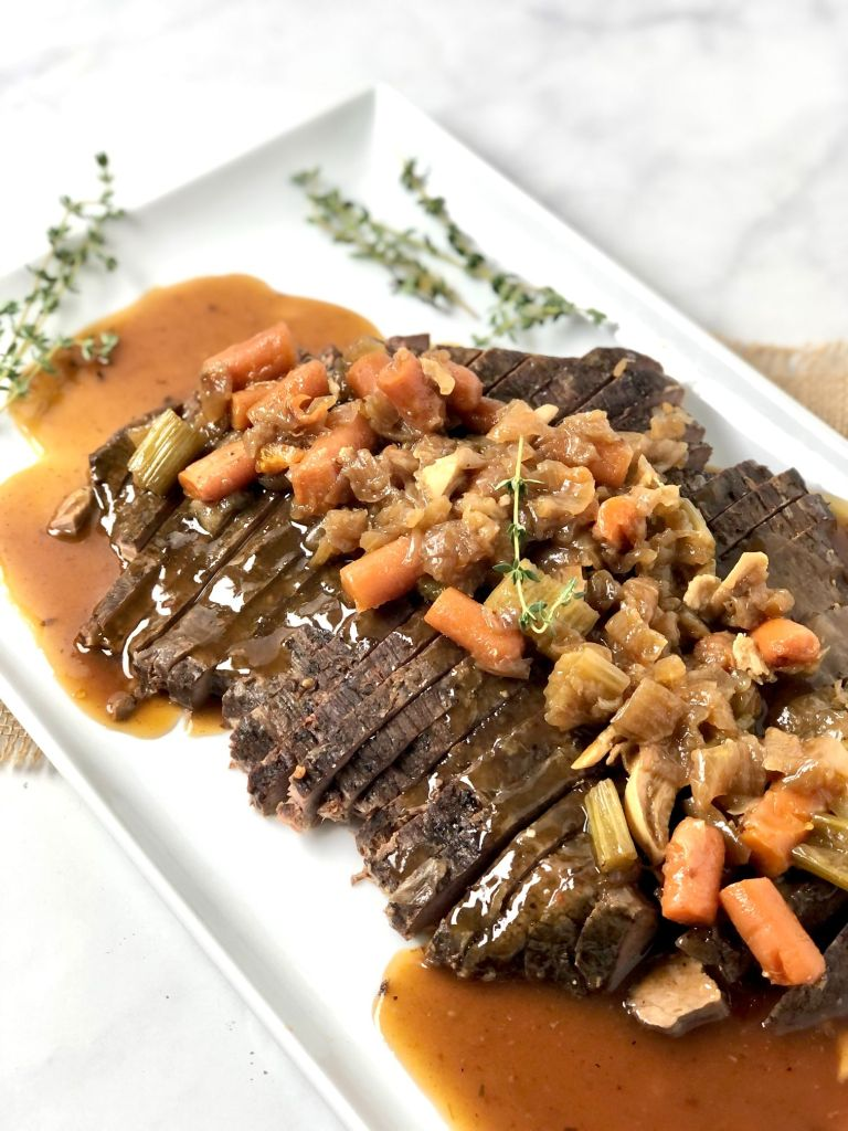 Picture of sliced beef brisket with thickened gravy and veggies on top