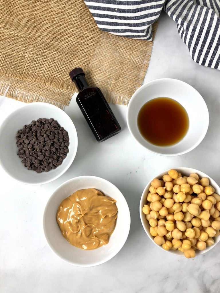 Overhead picture of ingredients for edible cookie dough including mini chocolate chips, vanilla, maple syrup, peanut butter and garbanzo beans