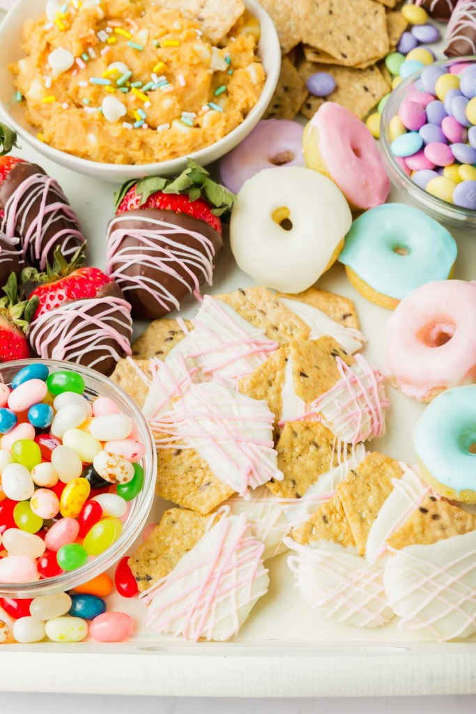 Picture of Easter snack board with chocolate covered strawberries, glazed donuts, edible cookie dough hummus and candies.