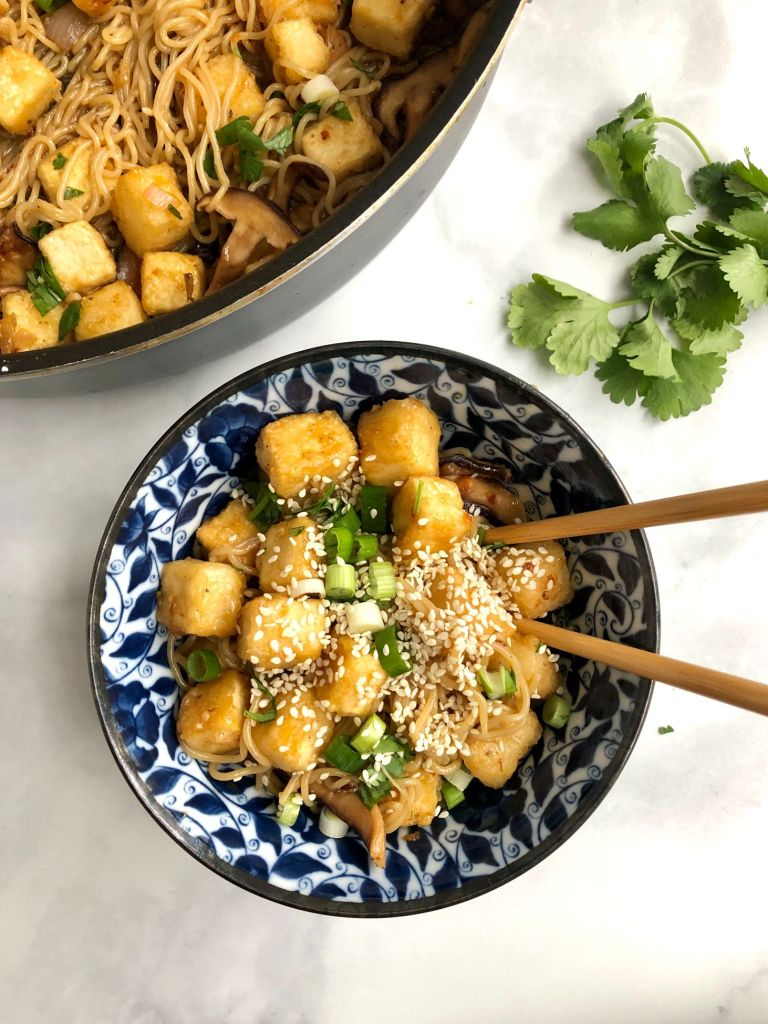 Crispy tofu and rice ramen in a bowl topped with sesame seeds, scallions and Asian sauce