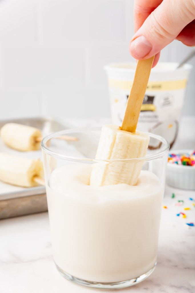 Dipping banana in tall glass of yogurt