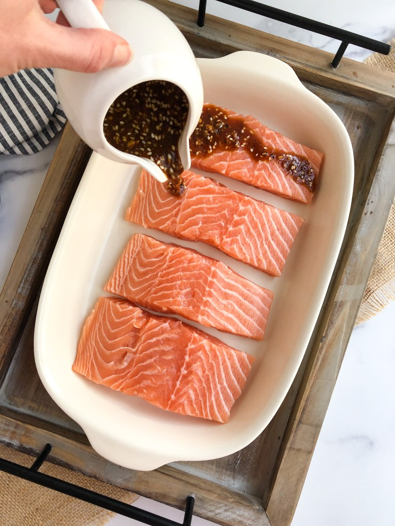 Pouring the Asian marinade over the salmon