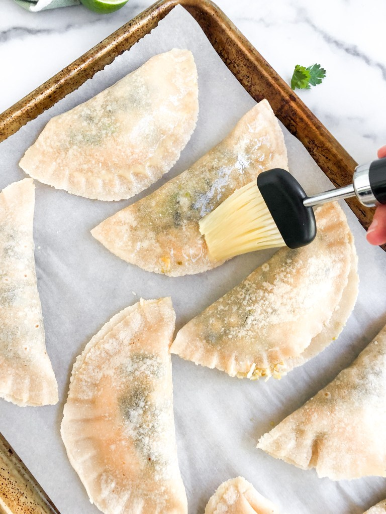 brushing tops of empanadas with egg to give them shine