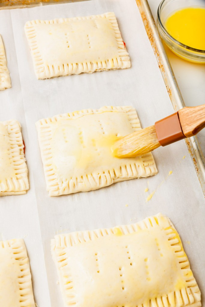 brushing tops of gluten-free pop tarts with egg wash