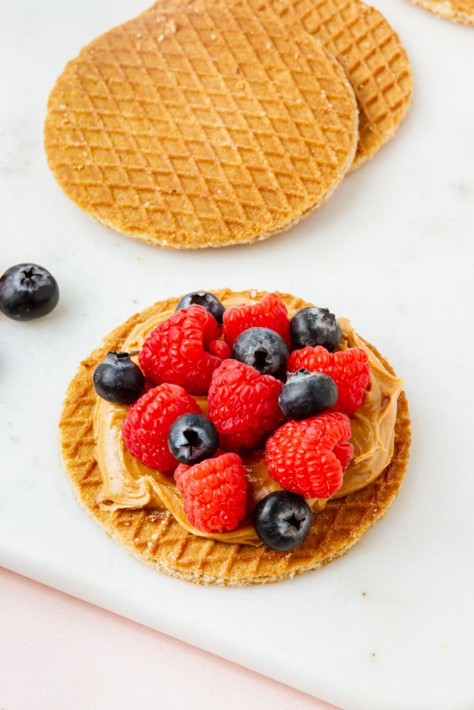 gluten-free stroopwafel topped with peanut butter and berries