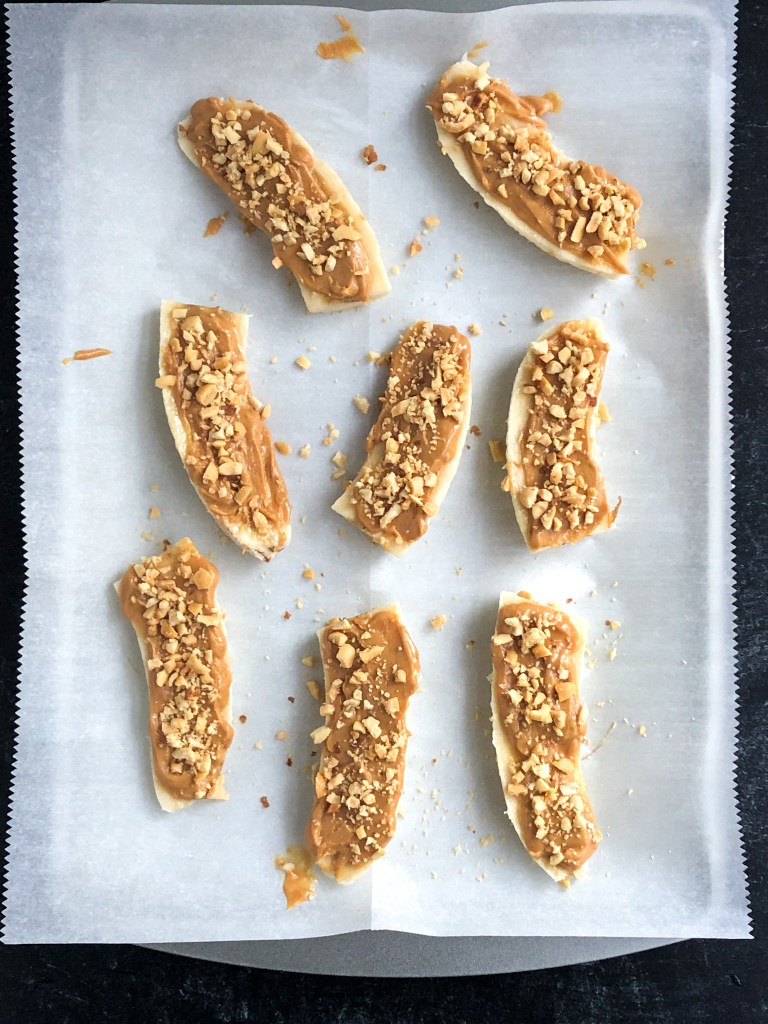 Bananas coated in peanut butter and crushed peanuts