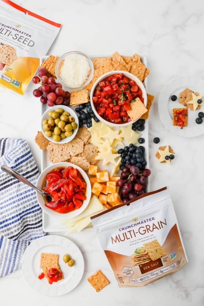 Gluten-free bruschetta snack board assembled with Crunchmaster crackers, cheeses, vegetables and fruits