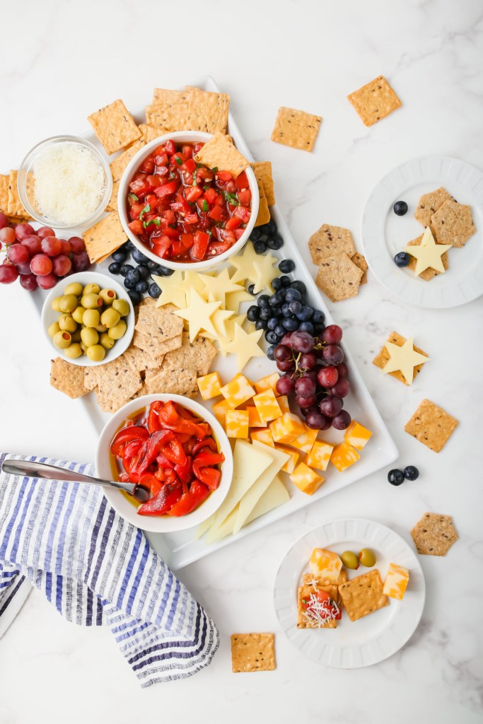 Picture of gluten-free bruschetta snack board assembled with crackers, cheeses, vegetables and fruits