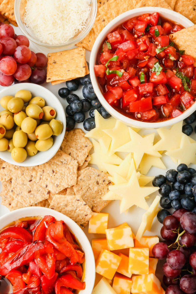 Upclose picture of 4th of July snack board with star-shaped cheeses, fruits and vegetables.