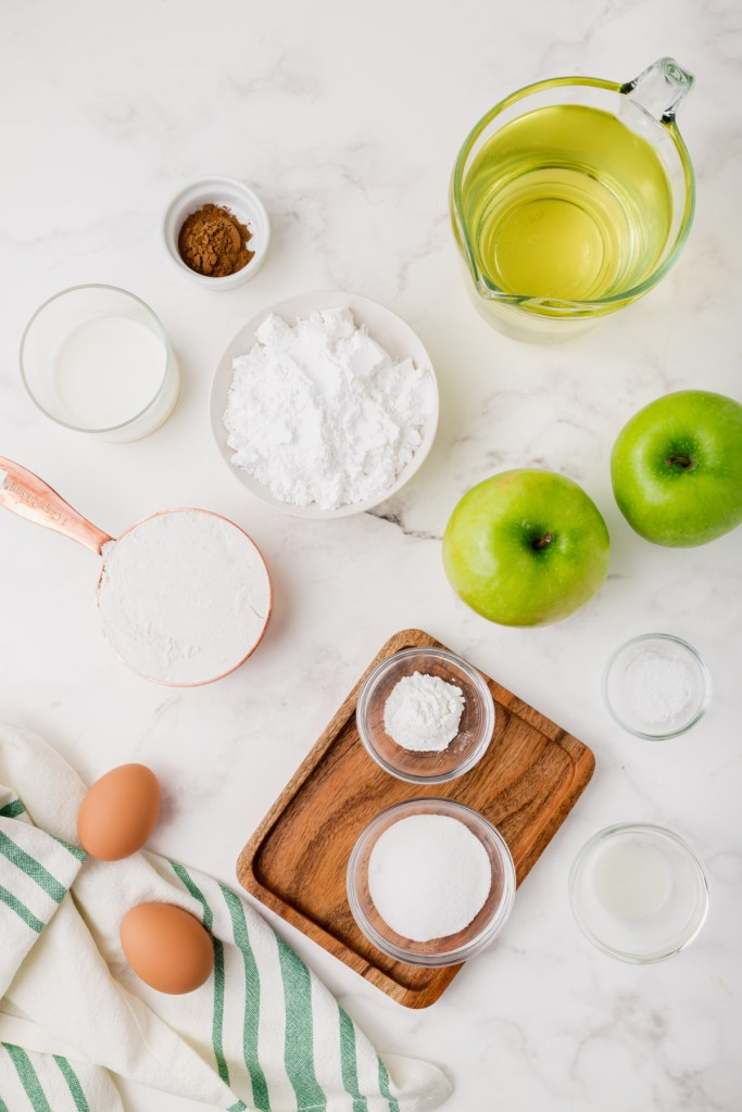 layout showing all the ingredients needed for gluten-free apple fritters recipe - apples, sugar, flour, eggs, etc.